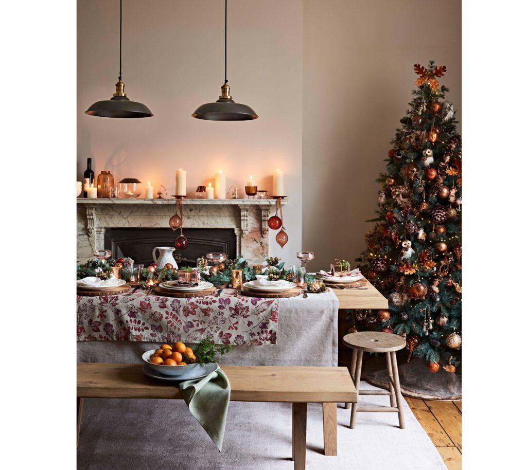vianočne vyzdobený interiér s vianočným stromčekom a slávnostne prestretým dreveným stolom vo vidieckom štýle