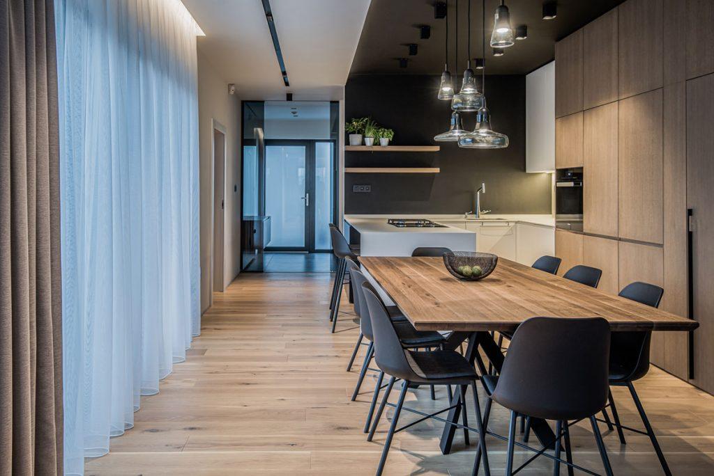 otvorená kuchyňa prepojená s jedálňou, zariadená s prírodnými materiálmi v modernom, minimalistickom štýle s bielou kuchynskou linkou, čiernym stropom, dyhovaným obkladom na stene a veľkým dreveným stolom pre širšiu rodinu