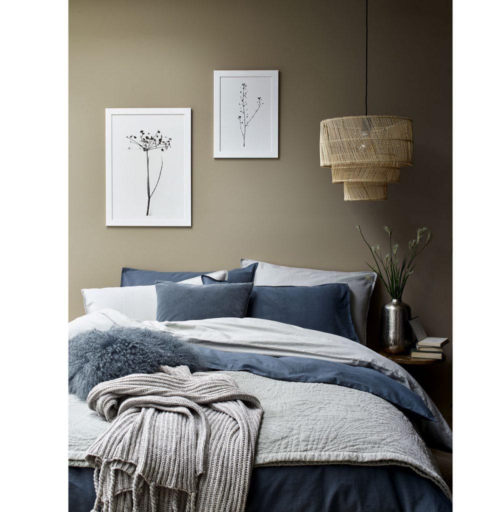 spálňa s posteľou, na ktorej sú navrstvené prikrývky rôznych materiálov a štruktúr, ladená do odtieňov modrej a sivej
