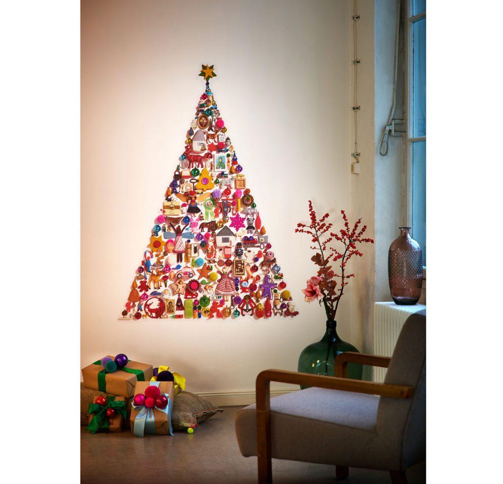 vianočný stromček vyrobený z rôznych ozdôb pripevnených na stenu do tvaru stromu