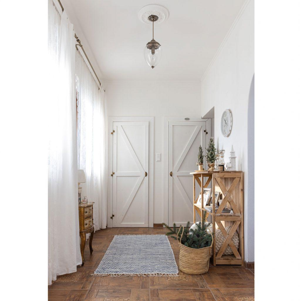 chodba v štýle farmhouse s vianočnými dekoráciami, dreveným regálom, pleteným košom, starožitným sekretárom a ručne vyrobenými dverami