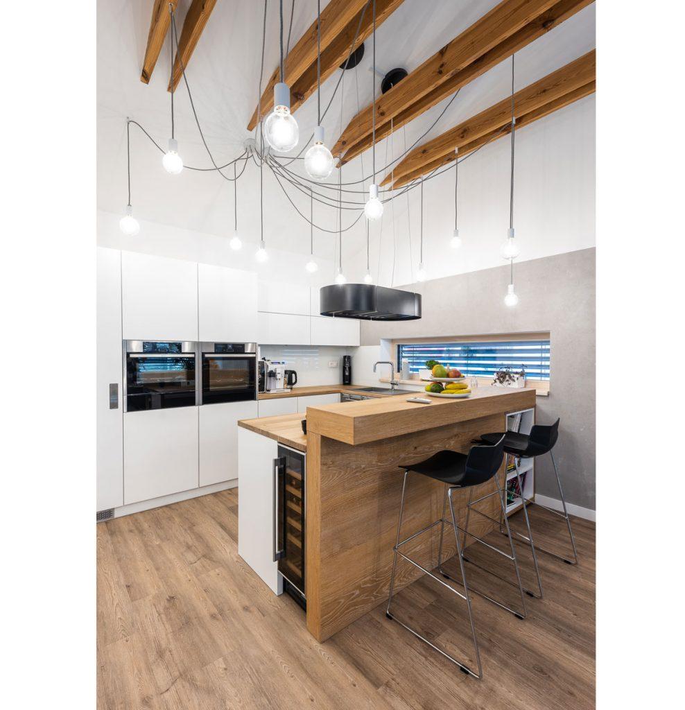 kuchyňa v industriálnom štýle s drevenými stropnými trámami, drevenou kuchynskou linkou v prírodnom dreve a bielej farbe, so vstavanými spotrebičmi, barovými stoličkami a vinotékou zabudovanou do ostrovčeka