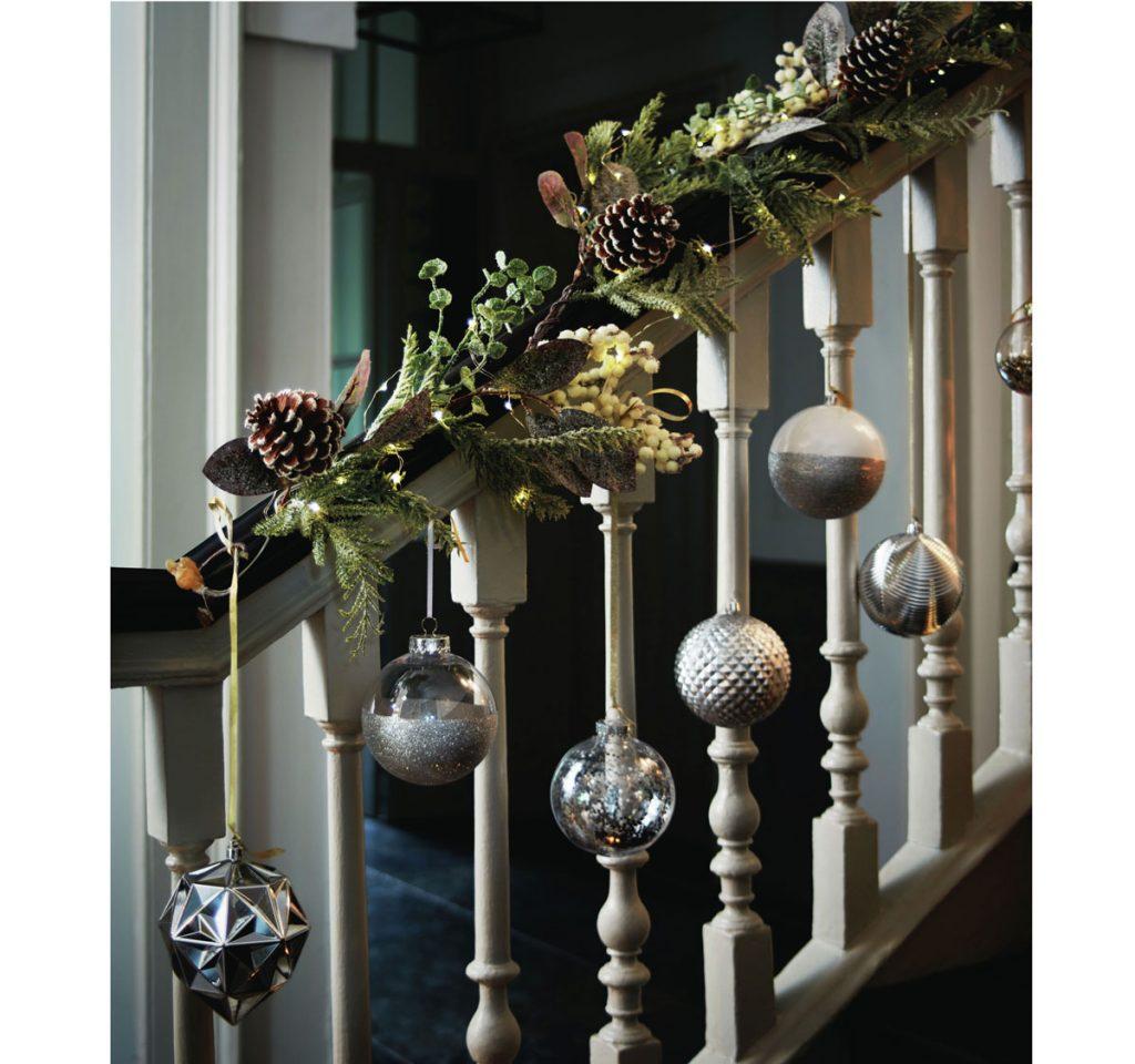 zábradlie schodiska obmotané s vianočnou výzdobou z vetvičiek, vianočných gúľ a šišiek