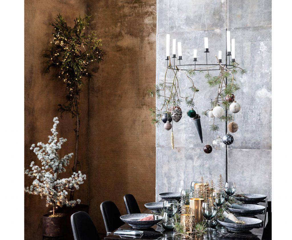 vianočne vyzdobený interiér s lustrom zdobeným ihličnatými vetvičkami a vianočnými guľami, vianočne prestretným stolom a s vianočným stromčekom so svetielkami