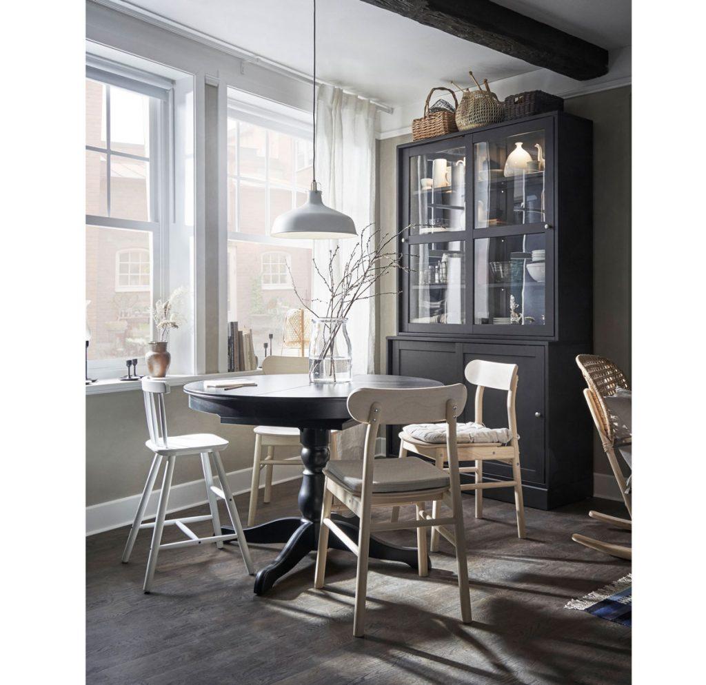 kuchyňa vo vidieckom štýle, s čiernym okrúhlym rozkladacím stolom a drevenými bielymi stoličkami, jednoduchým kovovým závesným svietidlom a čiernym príborníkom s presklenou vitrínou na riady
