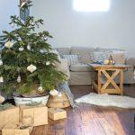obývačka vo farmhouse štýle s dreveným stolíkom, neutrálnou sedačkou, vianočným stromčekom, pleteným košom a kožušinou