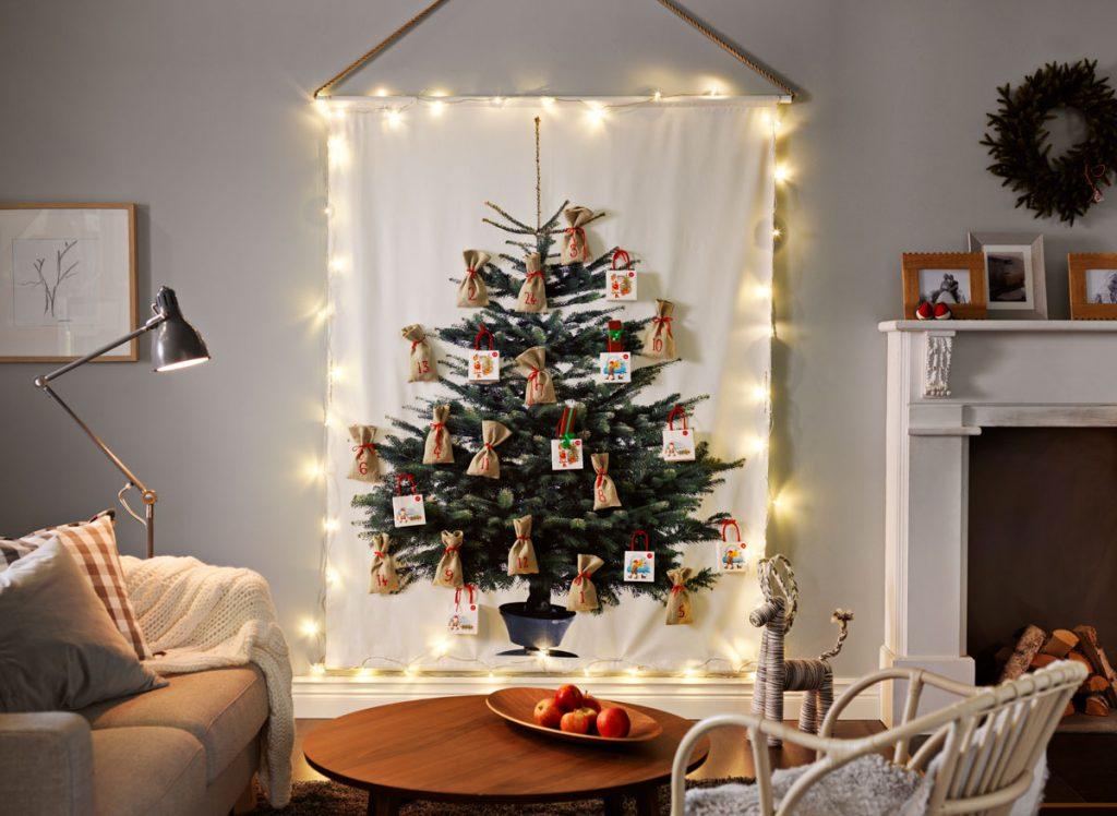 záves s motívom vianočného stromčeka, na ktorom sú pripevnené ešte vianočné ozdoby