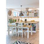 kuchyňa vo vidieckom štýle s industriálnymi prvkami, drevený stôl so stoličkami, s industriálnym lustrom, ostrovček s úložným priestorom na knihy a kuchynská linka v bielej farbe s tehlovým obkladom na stene