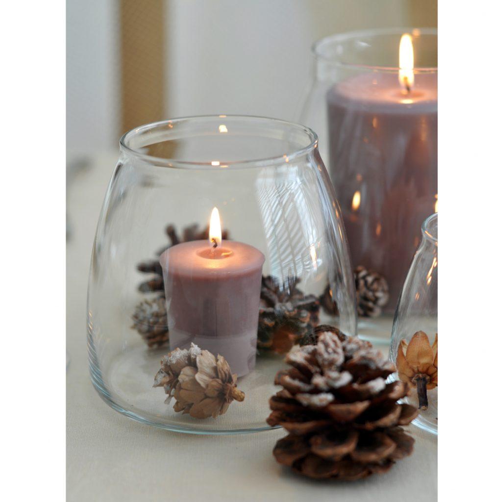 sklenené nádoby slúžiace ako svietniky na sviatočnom stole, vnútri je sviečka a šišky