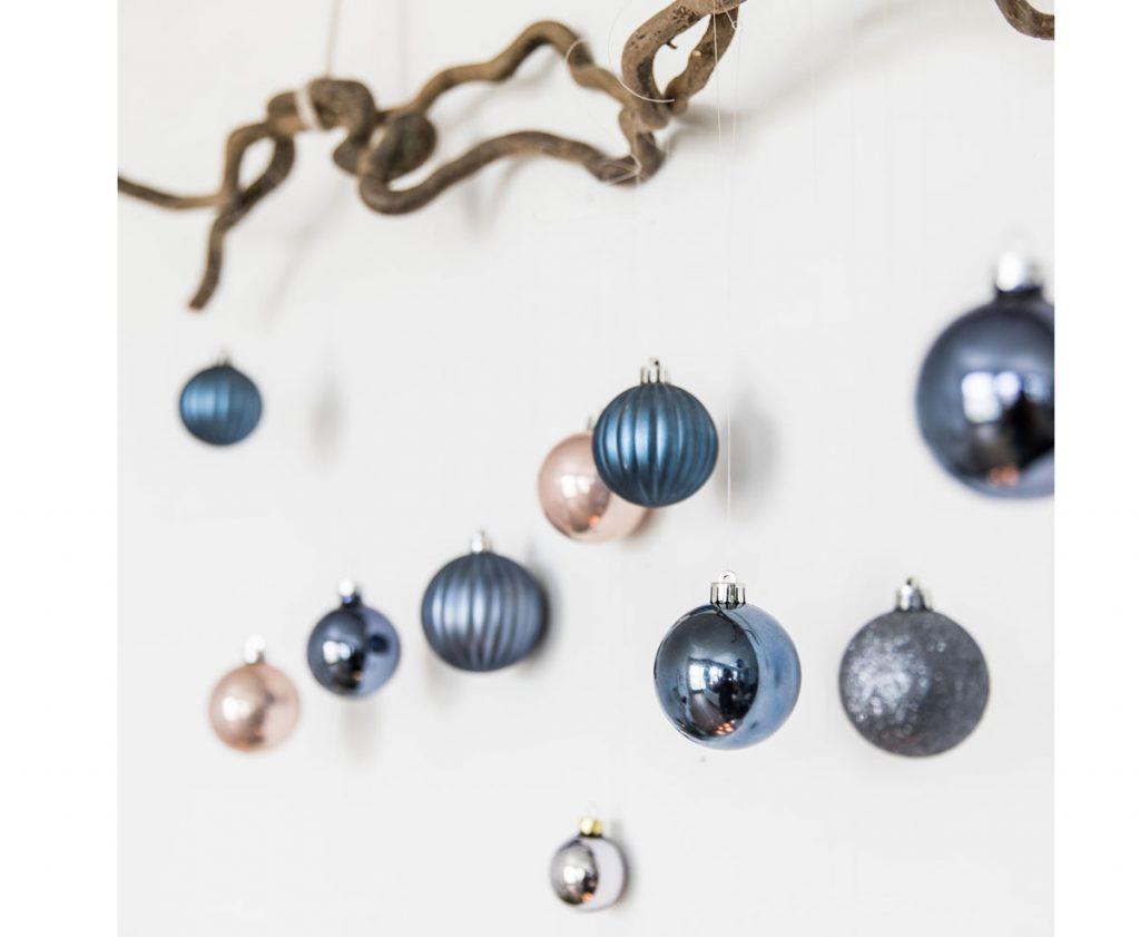 konár so zavesenými vianočnými guľami zdobí bielu stenu