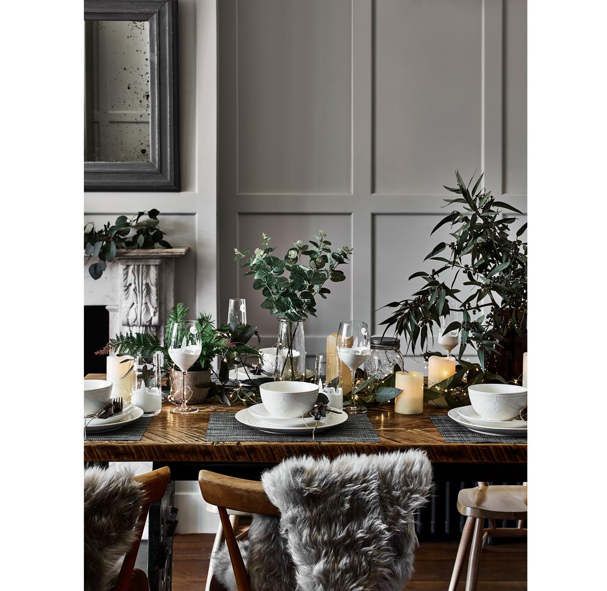 sviatočne prestretý stôl so svietnikmi, sviečkami, pohármi, riadmi a zeleňou v sklenených vázach a so stoličkami, na ktorých sú prevesené kožušiny