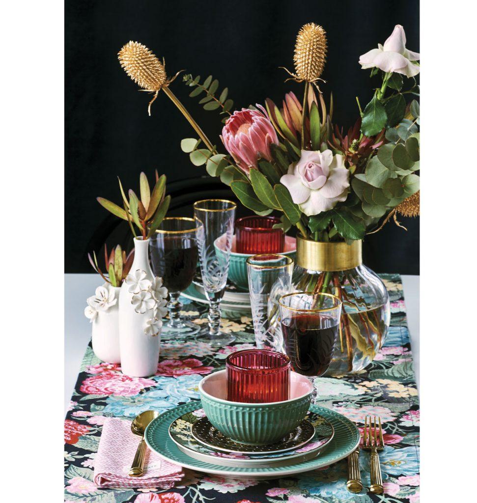 stôl s obrusom s farebným kvetinovým vzorom, sklenenými pohármi na víno a šampanské, so zelenými taniermi a miskami, zlatými príbormi a sklenou vázou s kvetinami