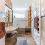 kúpeľňa v prírodných tónoch, s obkladom v imitácii dreva, vaňou, drevenými masívnymi policami, ohrievačom na uteráky a otvorenými drevenými policami