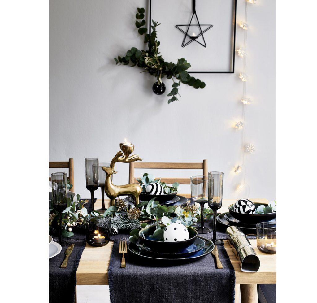 sviatočné prestieranie v tmavomodrej farbe s medenými dekoráciami a vianočnými vzorovanými guľami v bielo-čiernej kombinácii