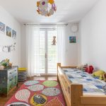 detská izba s farebnou maľovanou komodou, drevenou posteľou a farebným kobercom