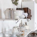 kuchyňa s otvorenými bielymi policami, na ktorých sú riady vo vidieckom štýle a svetelná girlanda vyrobená z vykrajovačiek na pečenie