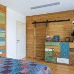 spálňa s dreveným obkladom na stene, posuvnými dverami vedúcimi do šatníka a s farebnou drevenou komodou