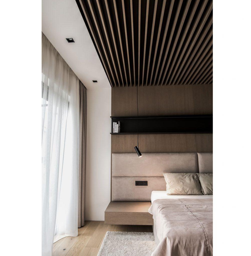 spálňa v modernom, minimalistickom štýle s vysokým čalúneným čelom neutrálne ladenej manželskej postele