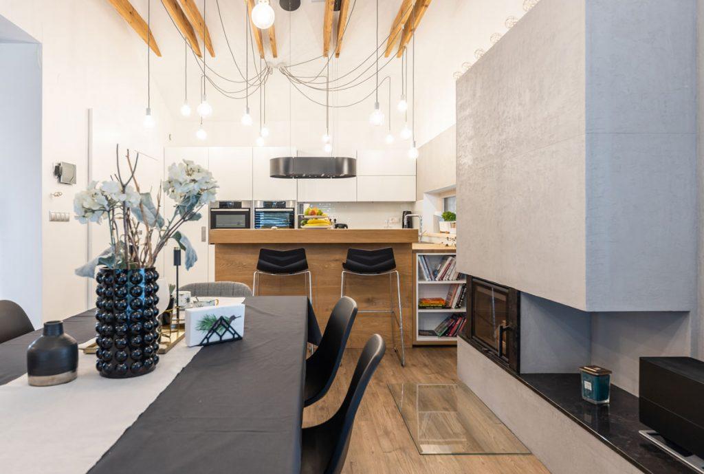 otvorený priestor kuchyne a jedálne v industriálnom štýle ladený do čiernej, bielej a hnedej farebnosti, so stropnými trámami a kozubom