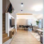 otvorený priestor obývačky, jedálne a kuchyne v industriálnom a minimalistickom štýle ladený do dreva, bielej a čiernej farby s točitým schodiskom na druhé podlažie