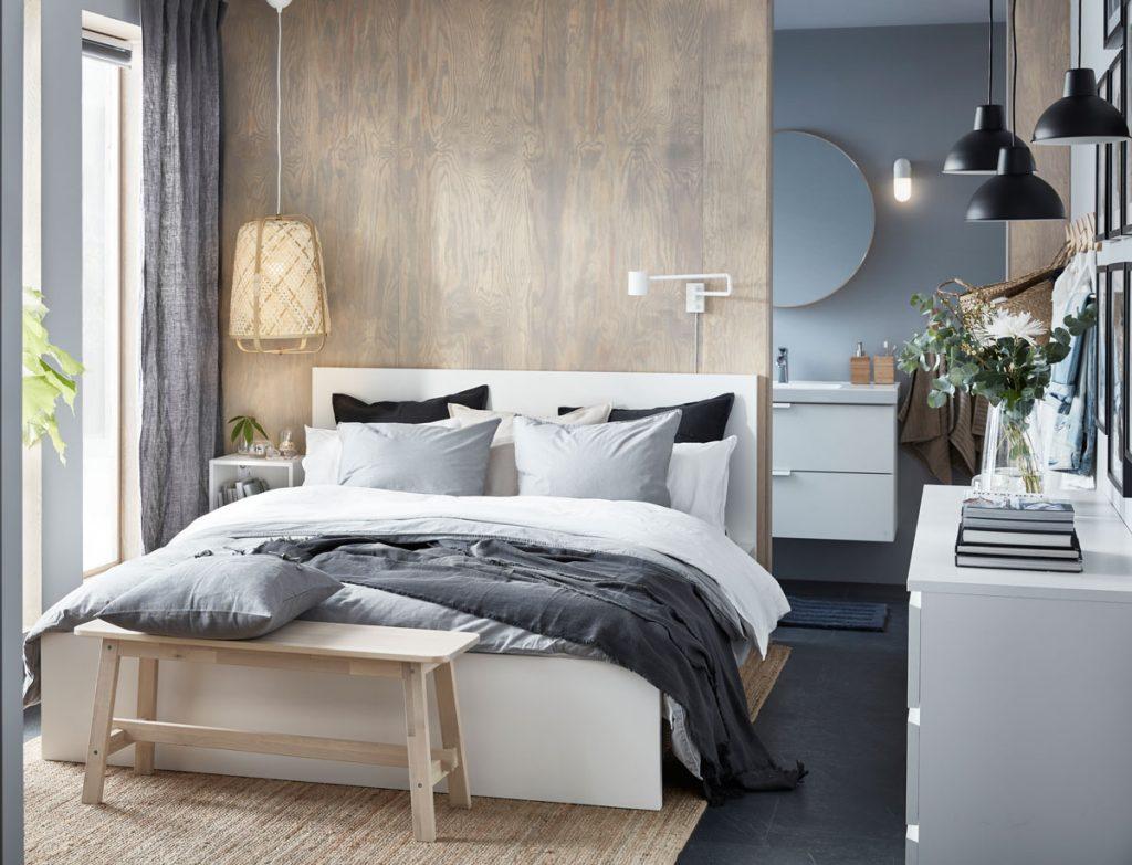 spálňa v natur štýle s prírodným kobercom, drevenou posteľou a obliečkami v odtieňoch modrej a bielej