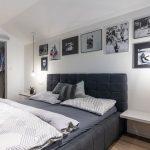 spálňa v minimalistickom industriálnom štýle so šatníkom a čalúnenou tmavou posteľou a s jednoduchými svietidlami - žiarovkami