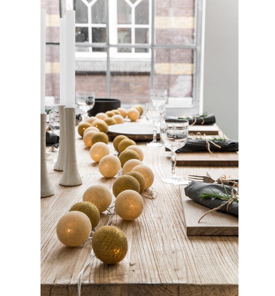 sviatočne prestretý stôl v prírodnom štýle so svetelnou reťazou umiestnenou cez stred stola