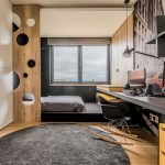 chlapčenská izba s výklenkom s posteľou oddeleným zčasti drevenou perforovanou zástenou, s bielou vstavanou skriňou a pracovným stolom, interiér je ladený v odtieňoch čiernej, hnedej s výraznou žltou