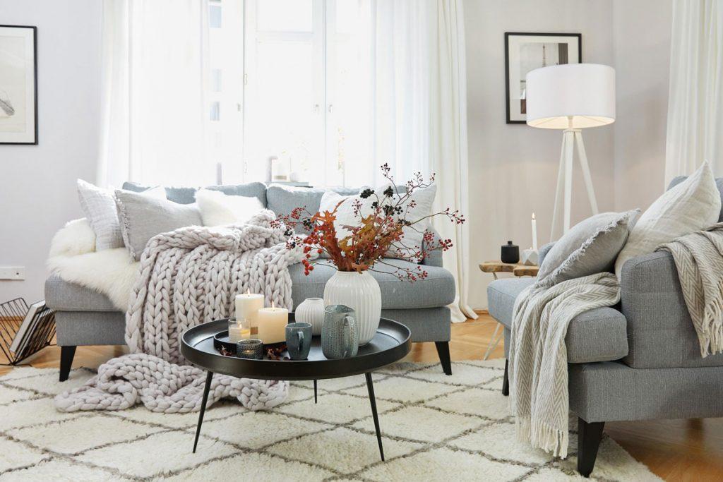obývačka v hygge štýle so sivou sedacou súpravou, vankúšmi v odtieňoch sivej a bielej z prírodných materiálov, pletenou vlnenou dekou, okrúhlym čiernym stolíkom a bavlneným bielym kobercom s geometrickým vzorom