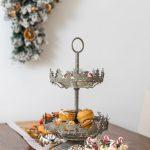 vianočný kovový etažér so sobmi, v ktorom sú poukladané koláče, v pozadí visí na stene vianočná girlanda