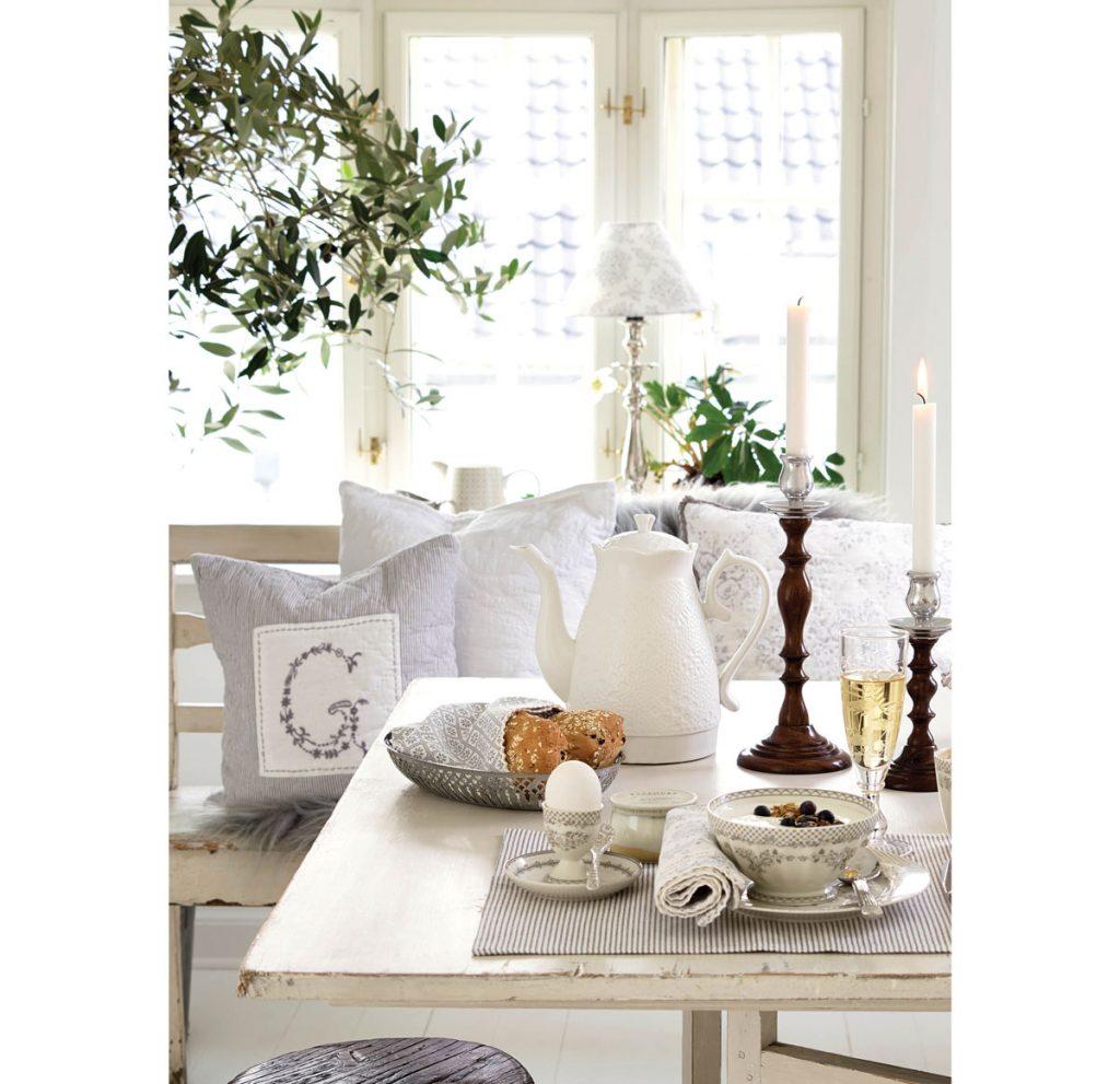 shabby chic interiér s bielym stolom, na ktorom je postavený drevený svietnik, miska, stojan na vajíčko a čajová kanvica s čipkovaným vzorom, a s drevenou lavicou s vankúšmi