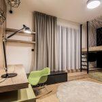 chlapčenská izba s dreveným stolom, zelenou hojdacou stoličkou a poschodovou posteľou s pódiom
