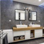 kúpeľňa so sivohnedým obkladom na stene a podlahe, s bielymi minimalistickými skrinkami, na ktorých stoja dve umývadlá