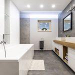 moderná kúpeľňa s bielymi skrinkami, na ktorých stoja dve umývadlá, oproti nim je veľká biela vaňa
