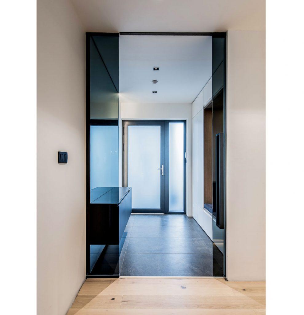 predsieň domu v minimalistickom dizajne osviežená veľkými zrkadlami na šatníkovej skrini