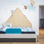 detská izba v minimalistickom štýle so sivomodrou posteľou a bočnou stenou v tvare domčeka a pomaľovanou stenou s detským motívom