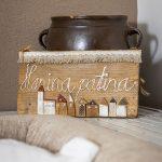 hlinená hnedá starodávna nádoba a drevená tabuľka s vyrezávanými domčekmi
