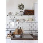 farmhouse kuchyňa s bielou kuchynskou linkou, otvorenými policami vyzdobenými závesnou svietiacou girlandou zhotovenou z kovových vykrajovačiek