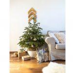 natur obývačka s gaučom v neutrálnej farbe, vianočným stromčekom, pleteným košom a darčekmi