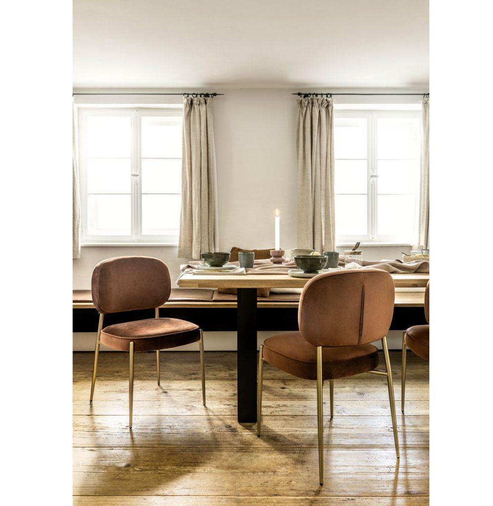 interiér s dreveným masívnym jedálenským stolom a zamatovými stoličkami v koňakovej farbe so zlatými nožičkami
