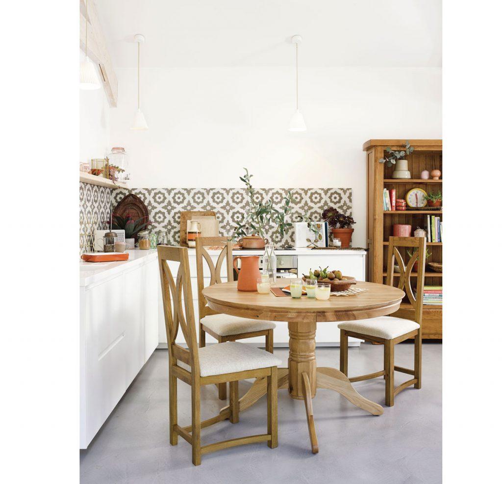 kuchyňa v modernom vidieckom štýle s dreveným okrúhlym stolom a stoličkami, bielou kuchynskou linkou do L a drevenou policovou skriňou