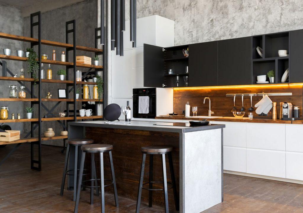 kuchyňa v industriálnom štýle s dreveno-kovovým regálom, bielo-čiernou kuchynskou zostavou, barovými stoličkami a kuchynským ostrovom, ktorý zároveň slúži aj na stolovanie
