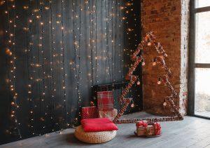 drevená silueta vianočného stromčeka omotaná svetelnou reťazou