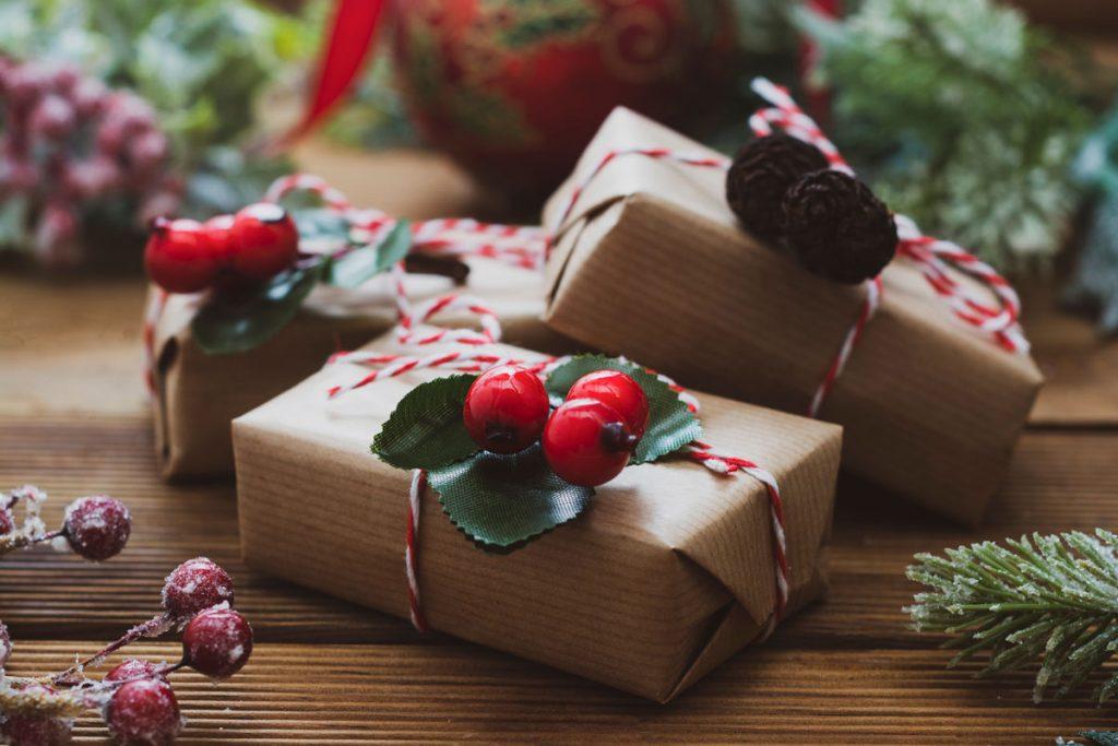 darčeky zabalené do recyklovaného hnedého papiera, previazané stuhou a dozdobené umelými vetvičkami a prírodnými šiškami