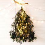 závesný vianočný stromček vyrobený z vetví ihličnanu, ktoré sú zavesené dole hlavou a podsvietené svetlom