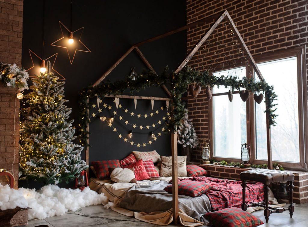 spálňa s vianočným bohato zdobeným stromčekom, svietidlami v tvare hviezdy a drevenou konštrukciou v tvare domčeku nad posteľou s girlandami z vetvičiek a hviezdičkovými reťazami
