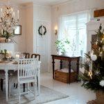 útulný vianočný interiér zariadený v škandinávskom duchu, s vianočným živým stromčekom v kvetináči, dreveným starodávnym stolíkom, pod ktorým je drevená debnička, s jedálenským stolom sviatočne ozdobeným a s drevenými stoličkami v hnedej a bielej farbe