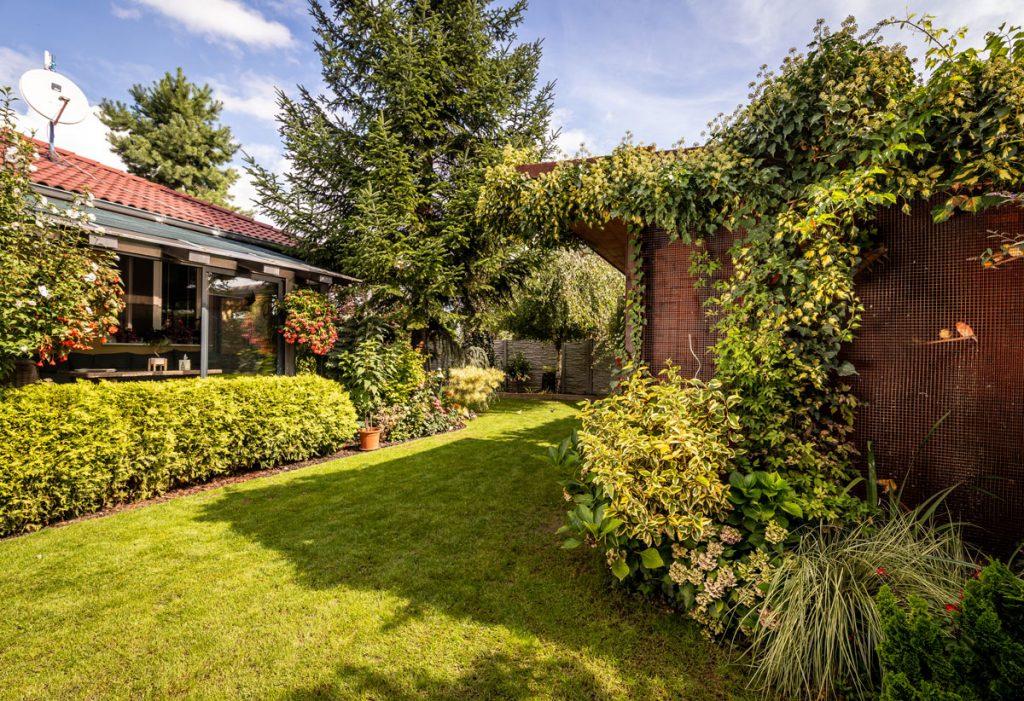 rodinný dom so záhradou s okrasnými trvalkovými záhonmi a voliérou pre vtáctvo