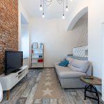 obývacia izba v malom byte v kombinácii industriálneho a severského štýlu so sivou pohovkou, stolíkom, behúňom, TV, policami, tehlovou stenou a pódiom na spanie