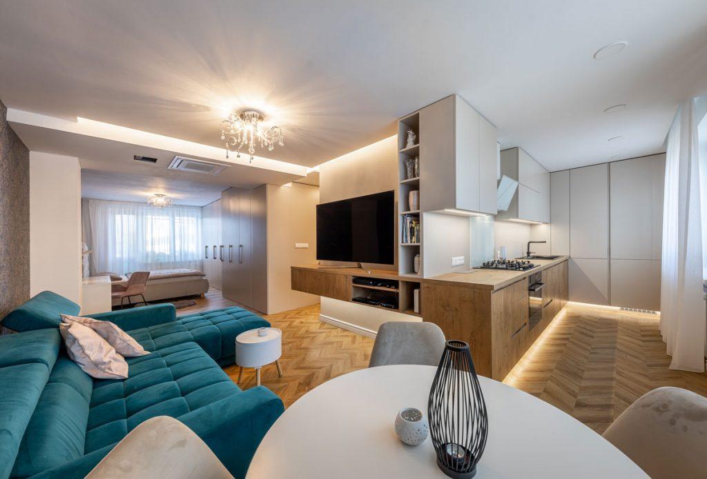 otvorený priestor jednoizbového bytu s modrou sedačkou, bielym jedálenským stolom, drevenou kuchynskou linkou prechádzajúcou do TV steny a neutrálnou spálňou so vstavanými skriňami
